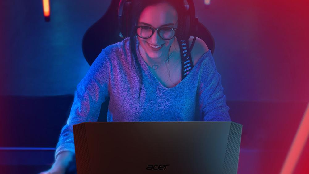 Naine, kes mängib Delli sülearvutil, kasutades hämaras keskkonnas kõrvaklappe