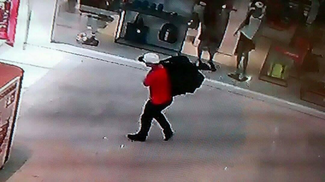 Pencuri dengan produk yang dicuri dari toko iPlace di Shopping Pelotas
